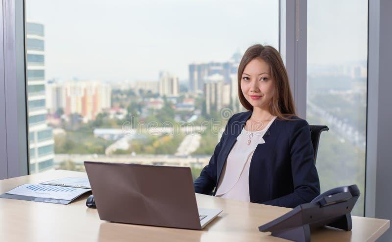 Junge asiatische Geschäftsfrau in der Klage, die an Laptop arbeitet stockfotos