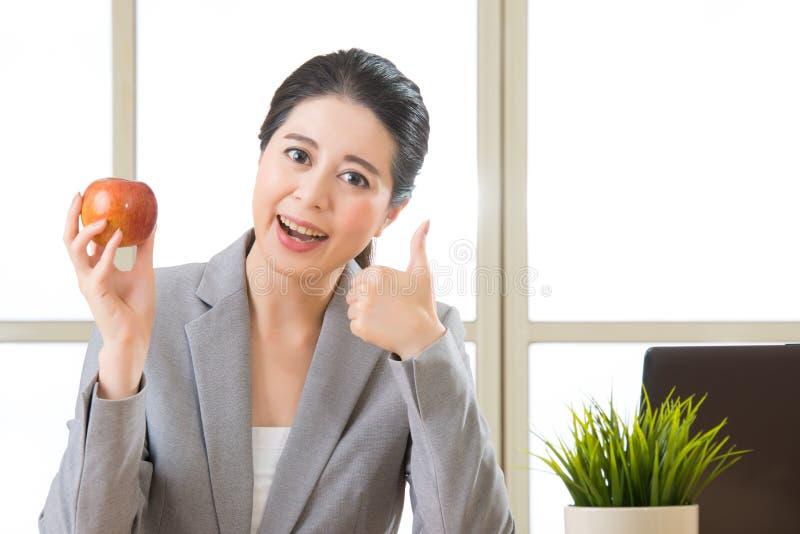 Junge asiatische Geschäftsfrau, die Apfel und Daumen hochhält stockfotografie