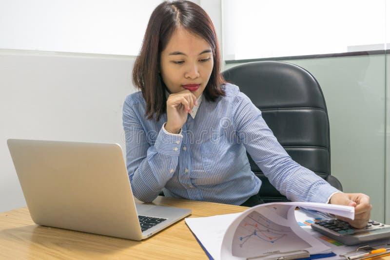 Junge asiatische Geschäftsfrau, die an Diagrammdokument im Büro arbeitet lizenzfreie stockbilder