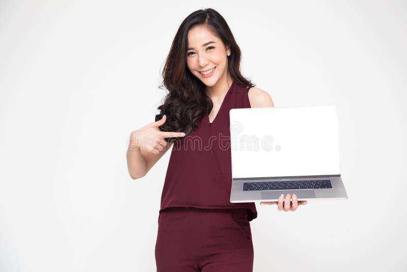 Junge asiatische Geschäftsfrau, die einen Laptop über weißem Hintergrund zeigt und Finger auf weißen Schirm des Notizbuches mit K stockbilder