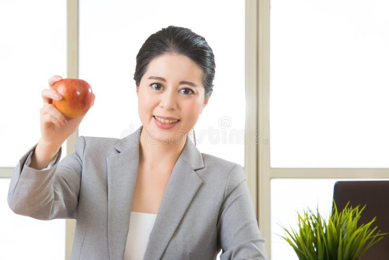 Junge asiatische Geschäftsfrau, die gesunden Snack, Apfel isst lizenzfreies stockfoto