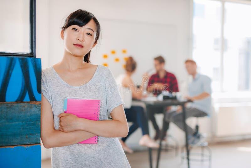 Junge asiatische Geschäftsfrau, die im Büro steht stockbild