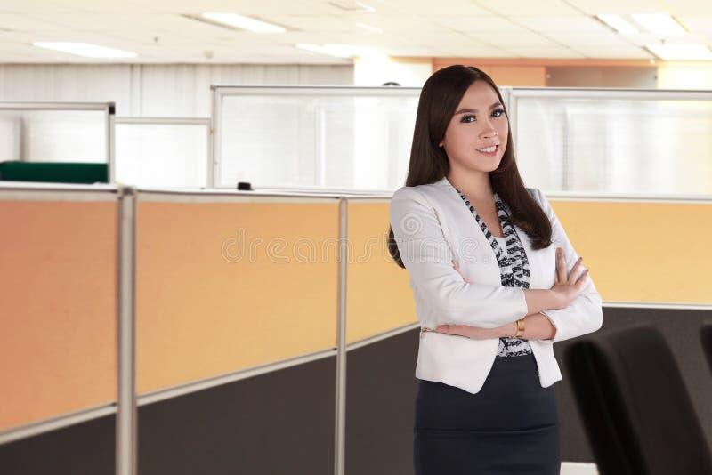 Junge asiatische Geschäftsfrau, die mit dem gefalteten Arm steht stockfotografie