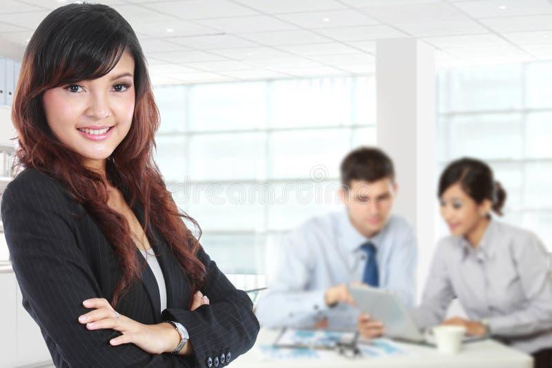 Junge asiatische Geschäftsfrau, die mit ihrem Sekretär hinten steht stockbilder
