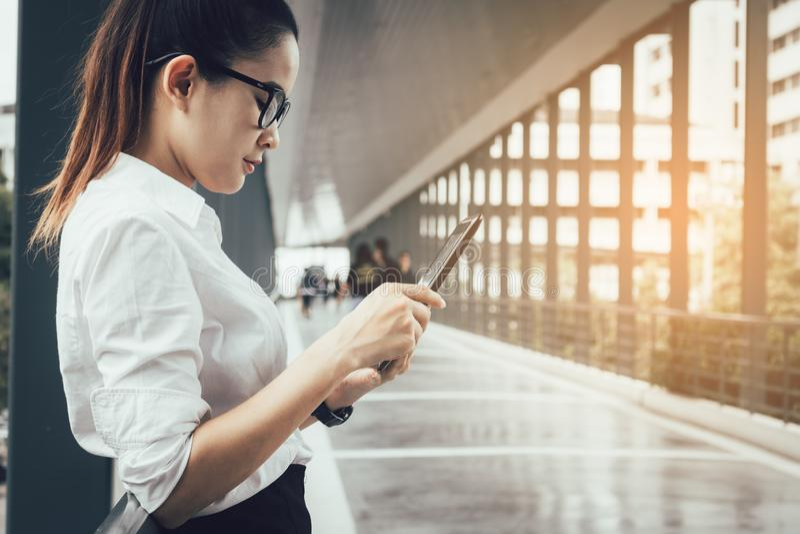 Junge asiatische Geschäftsfrau, die an Tablette in den Weisenbüro-BU arbeitet stockbild