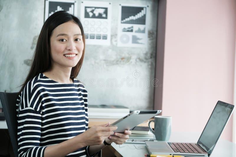 Junge asiatische Geschäftsfrau, die Tablette mit lächelndem Gesicht, positi verwendet stockfoto
