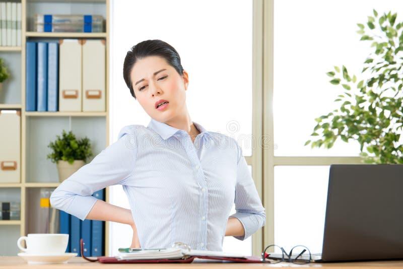 Junge asiatische Geschäftsfrau mit der Schmerz Rückseite herein stockfotos