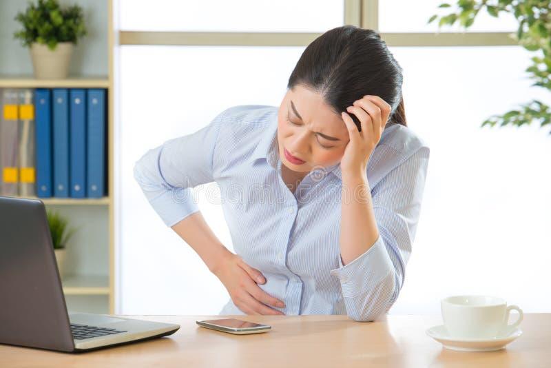 Junge asiatische Geschäftsfrau mit Magenschmerzen stockfotos