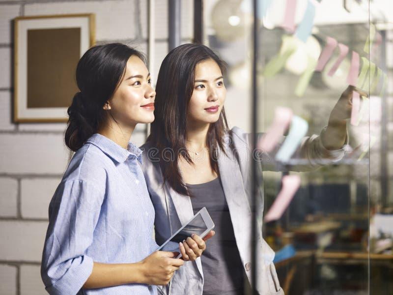 Junge asiatische Geschäftsfrauen, die Unternehmensplan im Büro besprechen lizenzfreie stockfotografie