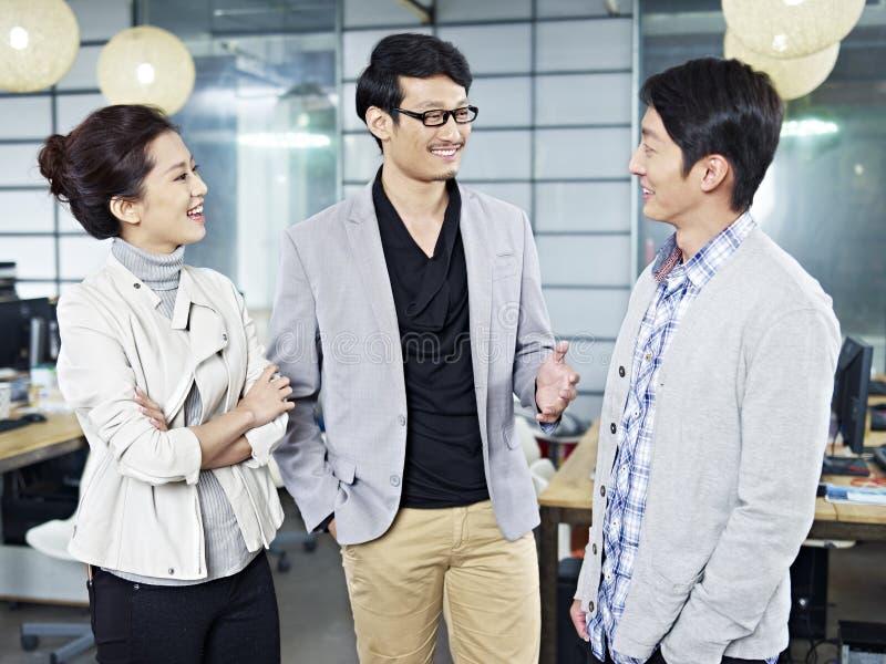 Junge asiatische Geschäftsleute, die im Büro sprechen lizenzfreies stockbild