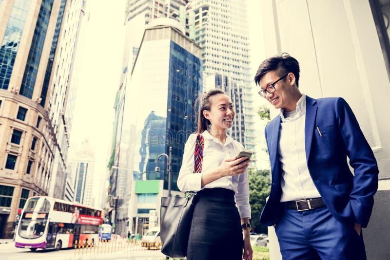 Junge asiatische Geschäftsleute in einer Stadt stockfotografie