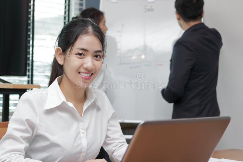 Junge asiatische Gesch?ftsfrau der F?hrung, die Kamera zwischen dem H?ren auf Darstellung im modernen B?rohintergrund betrachtet lizenzfreies stockfoto
