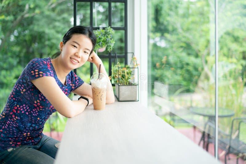 Junge asiatische hübsche zufällige Frau, die an der Kamera mit einer Schale Eiskaffee auf Holztisch in der Kaffeestube sitzt und  lizenzfreie stockbilder