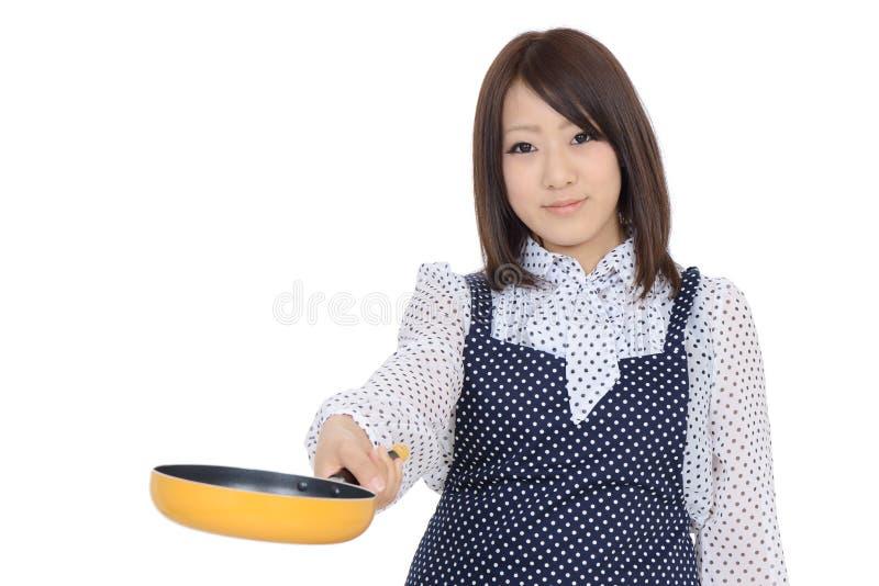 Junge asiatische Hausfrau, welche die Bratpfanne hält lizenzfreies stockbild