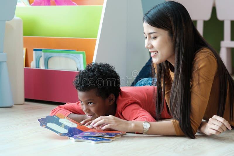 Junge asiatische Lehrerin und afrikanischer Junge in Kindergarten classr lizenzfreies stockfoto