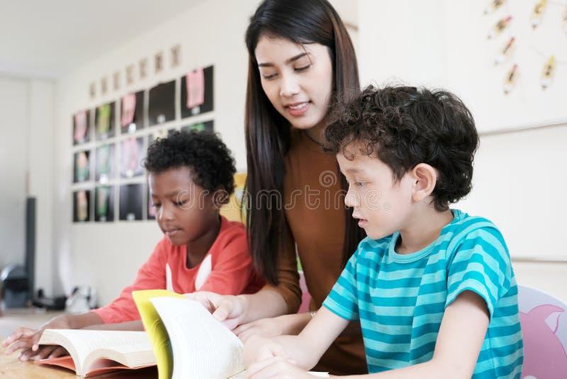 Junge asiatische Lehrerin und amerikanische, afrikanische Jungen im kinderga lizenzfreies stockbild