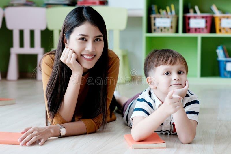 Junge asiatische Lehrerin und weißer Junge im Kindergartenklassenzimmer, Vorschulausbildungskonzept stockbild
