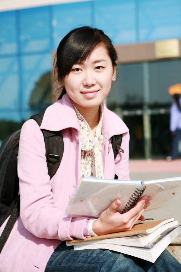 Junge asiatische Mädchenholdingbücher stockbild