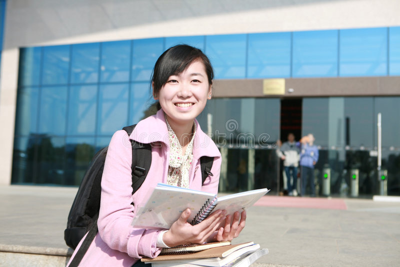 Junge asiatische Mädchenholdingbücher lizenzfreie stockbilder