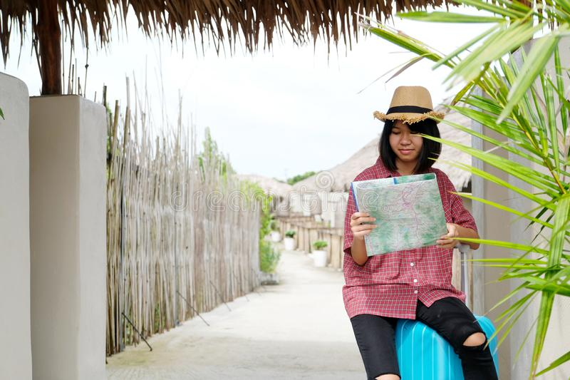 Junge asiatische Mädchenreisend-Holdingkarte und Sitzen auf Gepäck beim Reisen in der Landschaft im Freien, im Leutefrühling und  stockfoto