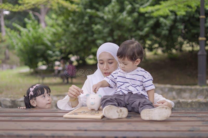 Junge asiatische Mutter ihre Kinder zu Rettungsgeld in Sparschwein für bessere Zukunft unterrichten stockbild