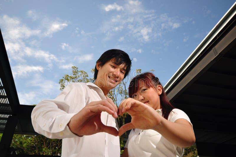 Junge asiatische Paare in der Liebe, die ein Inneres bildet, formen lizenzfreie stockfotografie