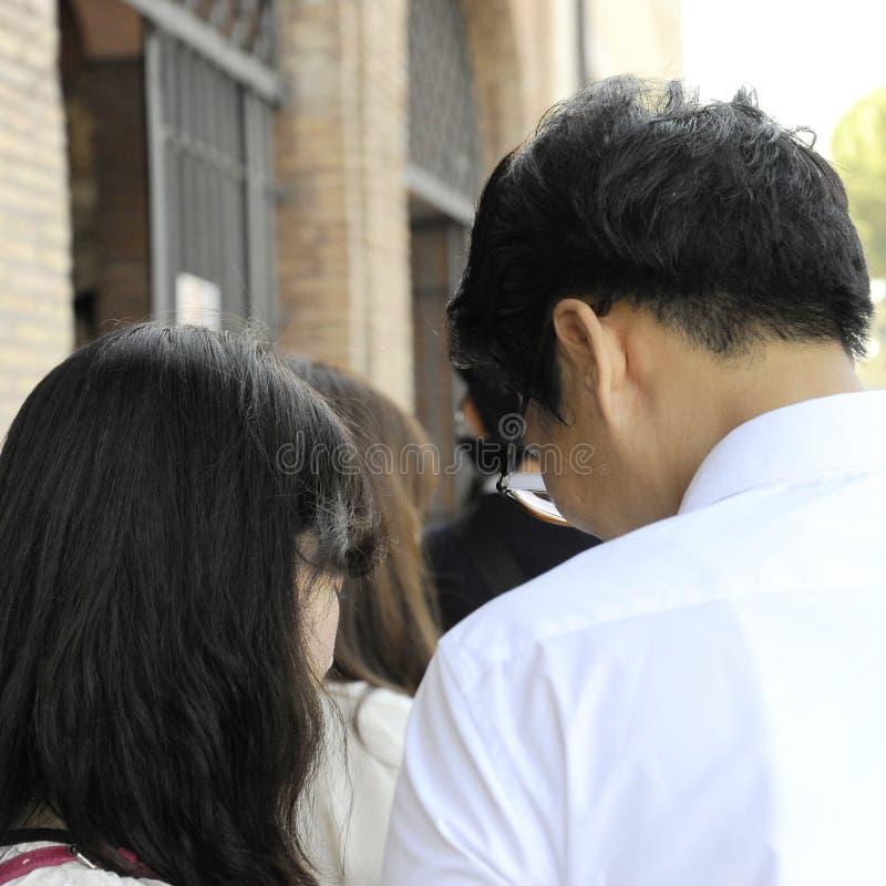 Junge asiatische Paare, die den Smartphone unter den Leuten aufpassen Schöne alte Fenster in Rom (Italien) lizenzfreies stockfoto