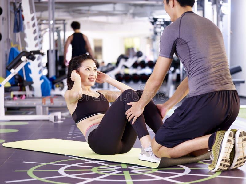 Junge asiatische Paare, die in der Turnhalle trainieren lizenzfreie stockbilder