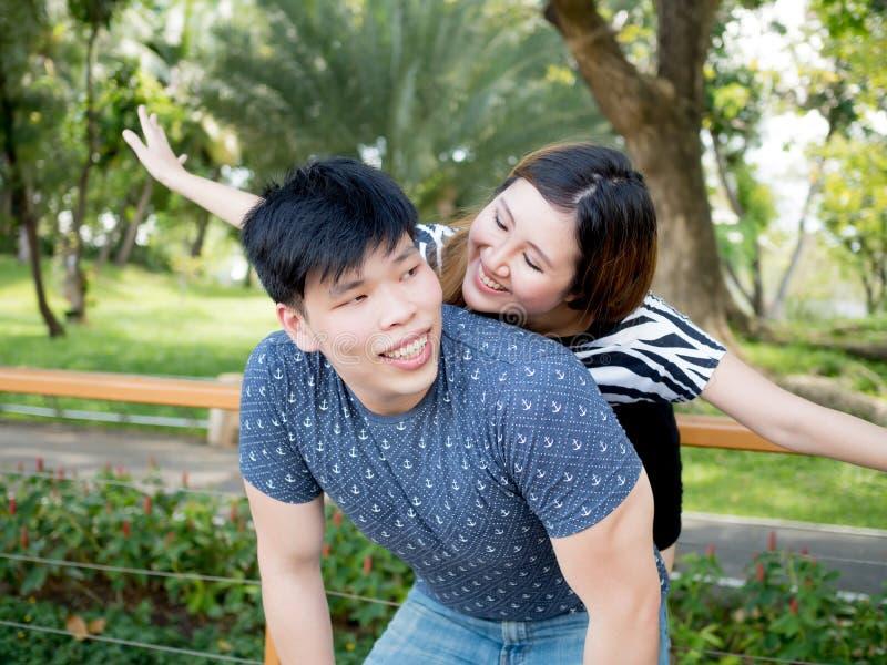 Junge asiatische Paare, die Doppelpol zusammen im grünen Naturba haben lizenzfreie stockbilder