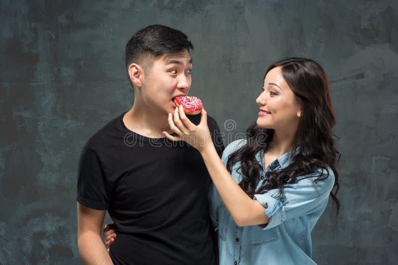 Junge asiatische Paare genießen das Essen des süßen bunten Donuts lizenzfreie stockbilder