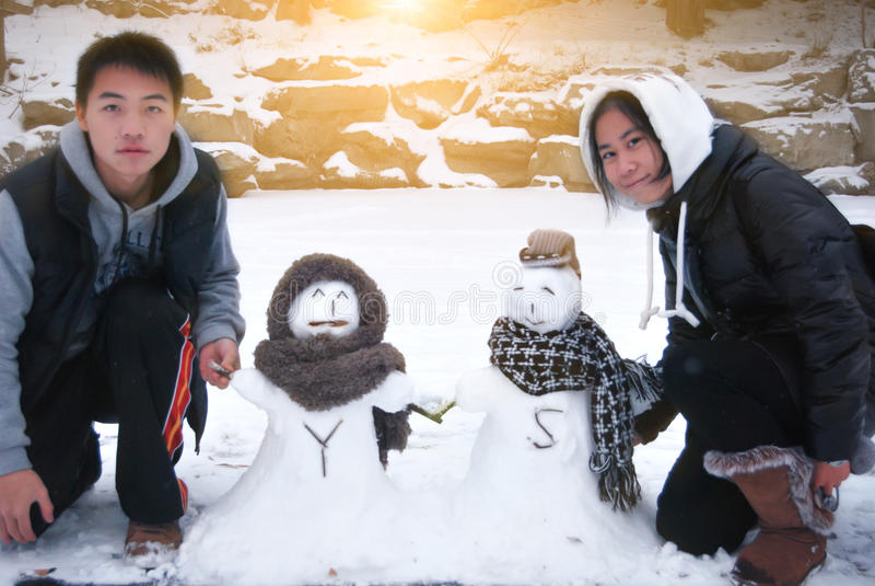 Junge asiatische Paare mit Snowmans lizenzfreies stockbild