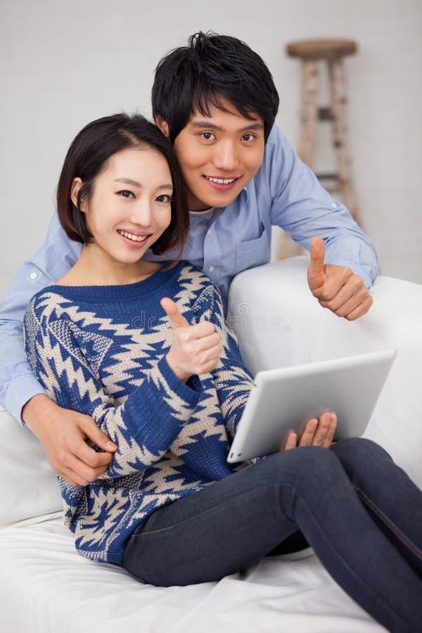 Junge asiatische Paare unter Verwendung der Auflage-PC- und -showdaumen stockbilder
