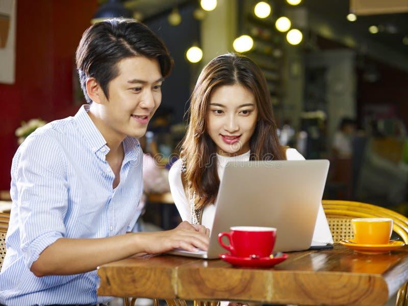 Junge asiatische Paare unter Verwendung des Laptops in der Kaffeestube stockfotos
