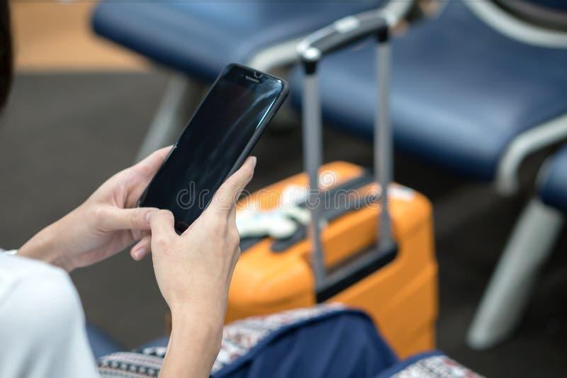 Junge asiatische Reisendfrau, unter Verwendung des Smartphone lizenzfreies stockbild