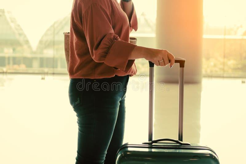 Junge asiatische Reisendfrauen und -gepäck an der Flughafenabfertigungsgebäudestellung am Flughafenholdingkoffer und am Gehen in  lizenzfreie stockfotografie