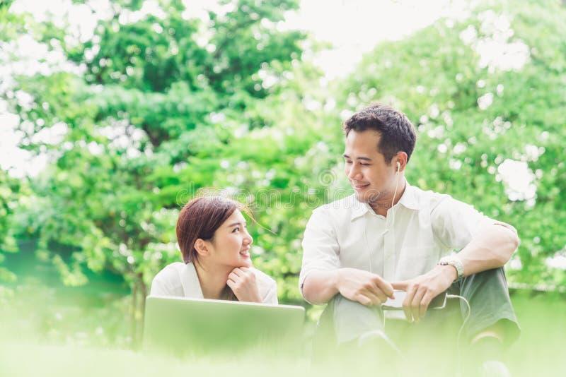 Junge asiatische reizende Paare oder Studenten betrachten einander im Garten oder im Park, unter Verwendung der Laptop-Computers  stockfotos