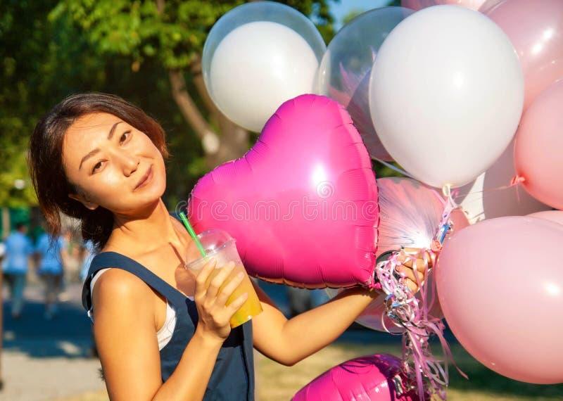 Junge asiatische Schönheit mit mehrfarbigen Ballonen des Fliegens in der Stadt stockfotografie