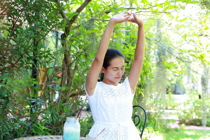 Junge asiatische sitzende Frau und am Café sich entspannen im Freien lizenzfreie stockfotos