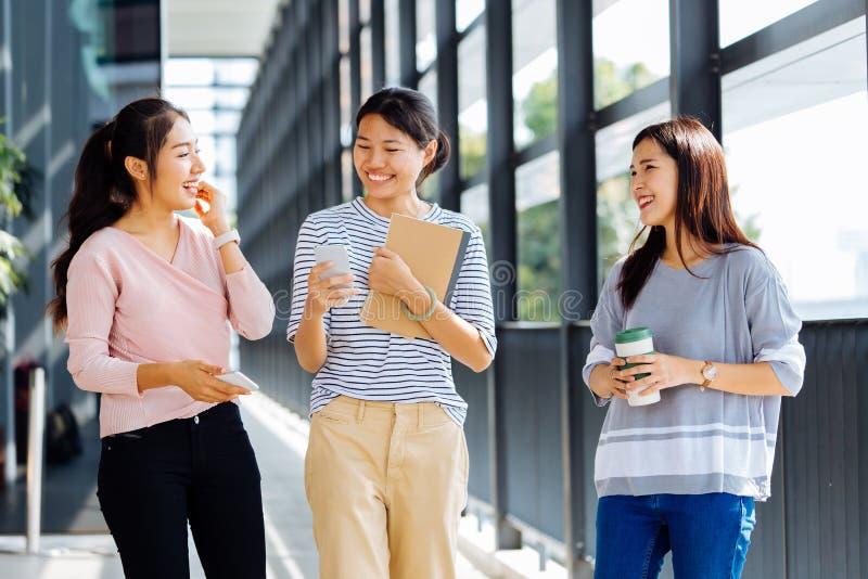 Junge asiatische sprechende Geschäftsfrauen beim Gehen in Bürogebäude in der Freizeitkleidung stockfoto