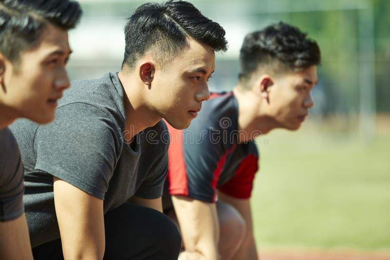 Junge asiatische Sprinter auf Anfangszeile stockbilder