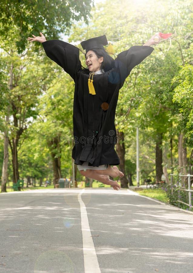 Junge asiatische Studentin des Glückes in ihrem Staffelungskleid und tragenden in Staffelungskappe mit Zertifikat in den Händen stockbild