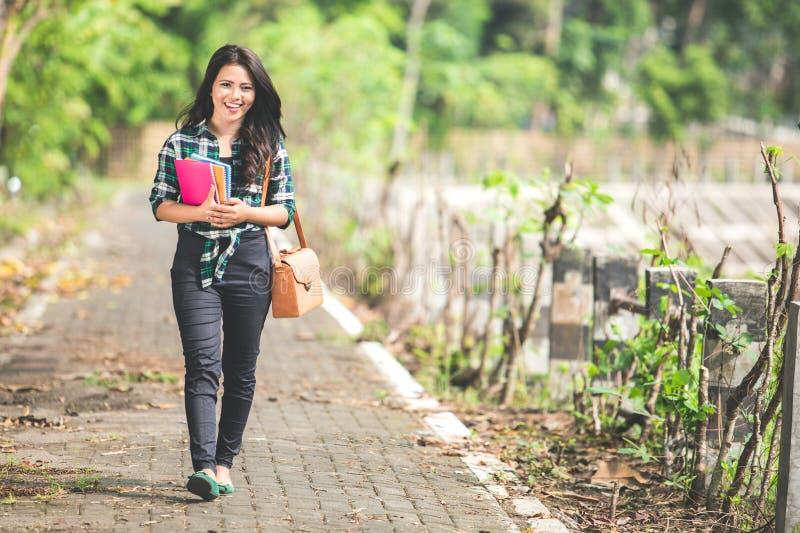 Junge asiatische Studentin, die Bücher beim Gehen auf das PA hält lizenzfreies stockbild