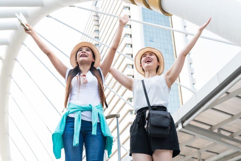Junge asiatische touristische Frauen, die aufwärts ihre Arme ausdehnen und Abstand mit lächelnden Gesichtern untersuchen stockbilder