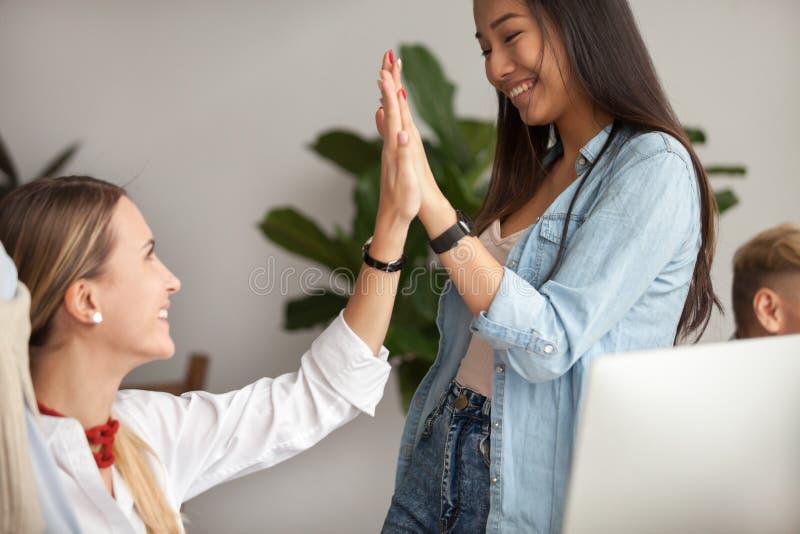 Junge asiatische und kaukasische Geschäftsfrauen, die hoch--fünf celebra geben stockfotografie