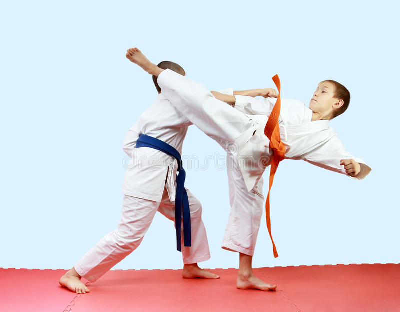 Junge Athleten bilden Schlagbeine und -arme auf den Matten aus stockbild
