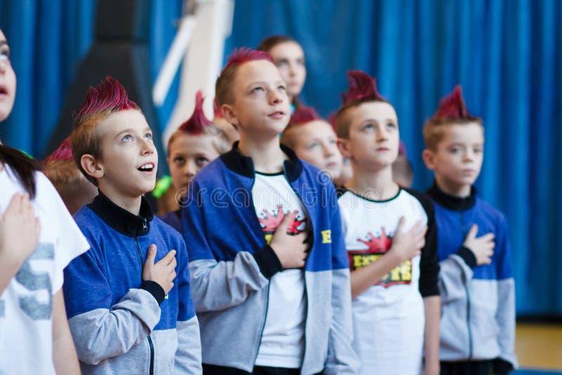 Junge Athleten hören auf das Nationalhymne, Ñ- hampionship der Stadt von Kamenskoye, beim cheerleading unter Soli, die Duos und  stockfotos