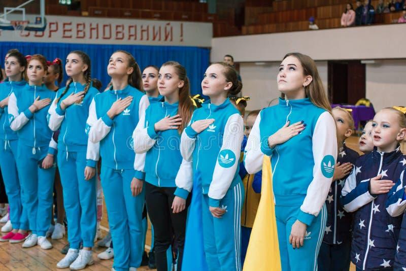 Junge Athleten hören auf die Nationalhymne, Meisterschaft der Stadt von Kamenskoye, beim cheerleading unter Soli, Duos und Teams lizenzfreies stockfoto