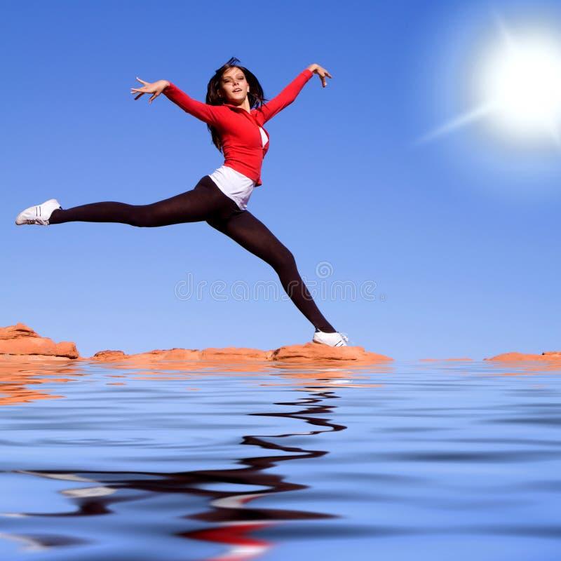 Junge athletische Frau, die auf das Wasser springt stockbild