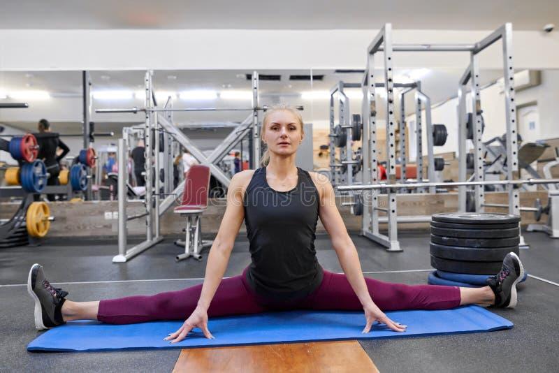 Junge athletische muskulöse Frau, die Training in der Turnhalle, übendes Yoga der Frau ausdehnend tut lizenzfreie stockfotografie