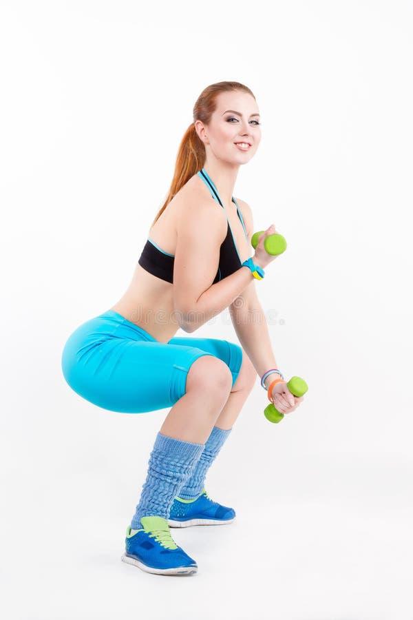 Junge athletische rothaarige Frau in der Sportkleidung, die Übung mit Dummköpfen tut stockfotografie